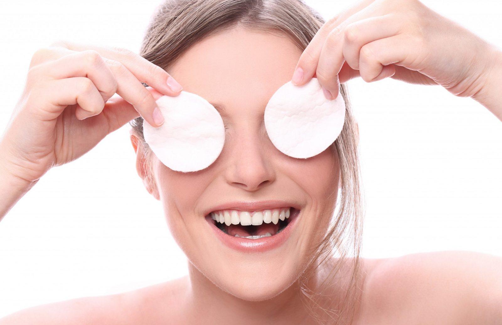jovem sorri com algodões nos olhos após peeling