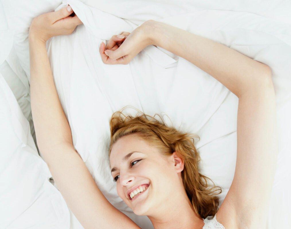 pós operatório da mamoplastia de aumento; senhora deitada a sorrir